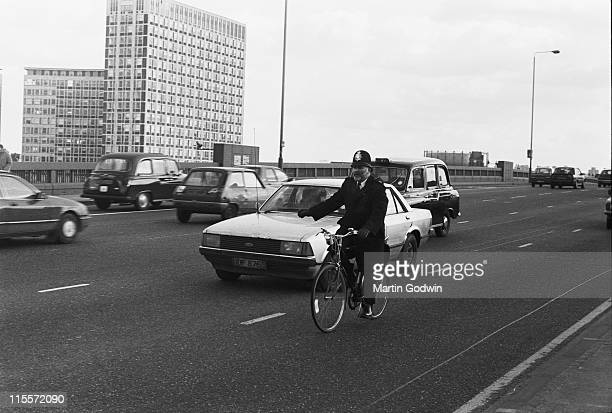 London Policeman in uniform with helmet cycling his bike across Vauxhall Bridge while indicating right with his arm with a Ford motor car...