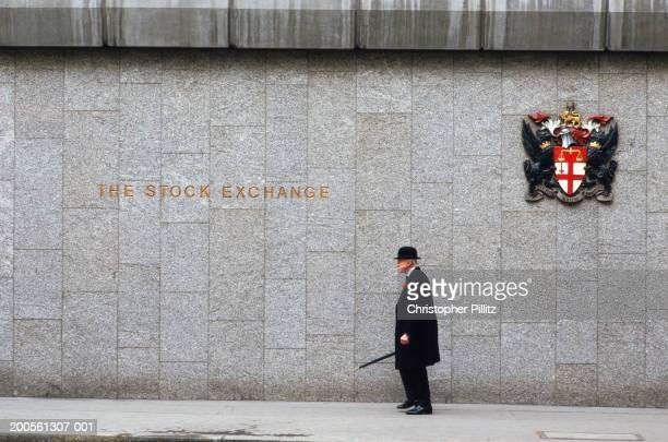 UK, London, senior man walking outside The Stock Exchange, side view
