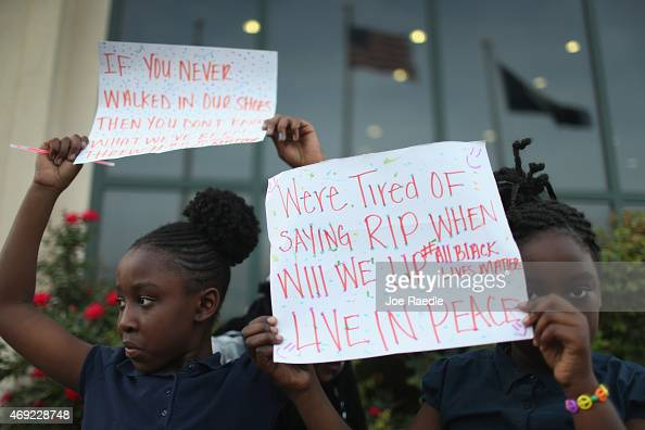 London Simmions and Nevaeh Purcell hold signs at a vigil in front of the North Charleston City Hall for Walter Scott on April 10 2015 in North...