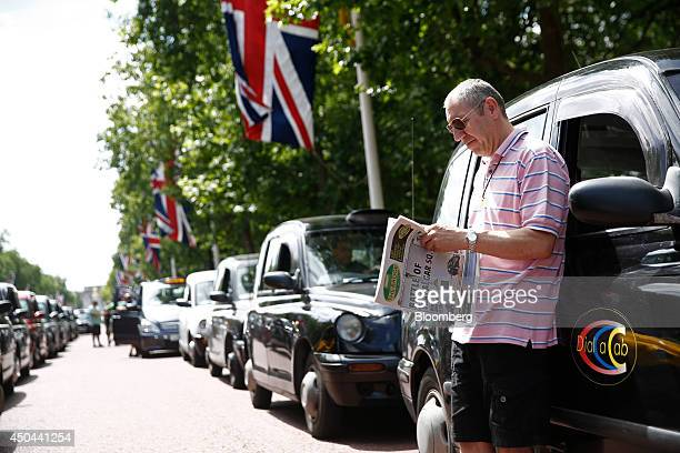 A London taxi driver leans against the diver's door of his cab as he reads 'The Badge' newspaper whilst parked along The Mall leading away from...