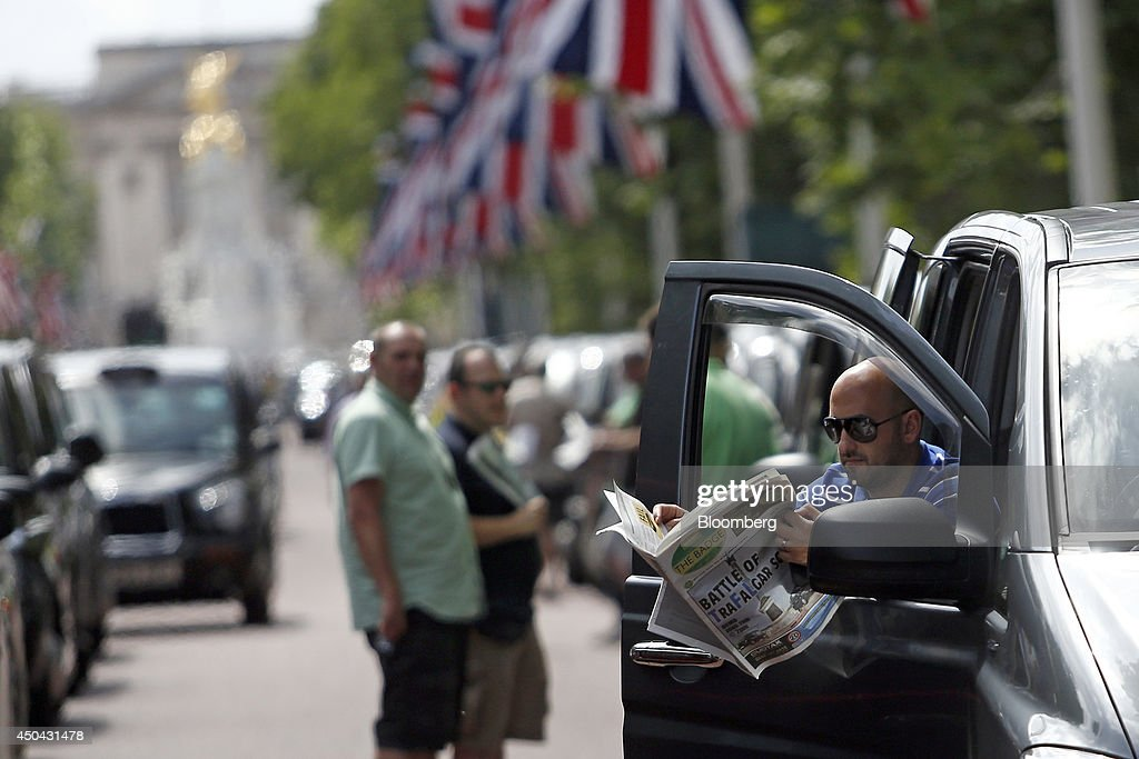 A London taxi driver leans on the driver's door of his cab as he reads 'The Badge' newspaper, whilst parked along The Mall, leading away from Buckingham Palace, during a protest against Uber Technologies Inc.'s car sharing service in London, U.K., on Wednesday, June 11, 2014. Traffic snarled in parts of Madrid and Paris today, with a total of more than 30,000 taxi and limo drivers from London to Berlin blocking tourist centers and shopping districts. Photographer: Simon Dawson/Bloomberg via Getty Images