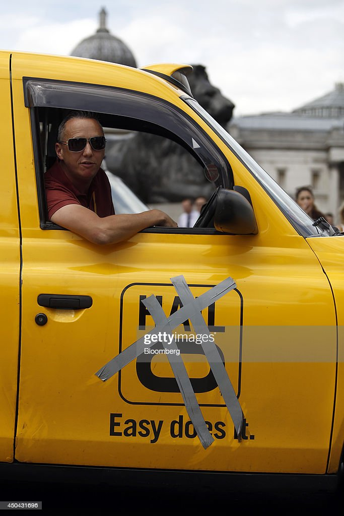 A London taxi driver leans out of the driver's window of his cab, above a partially covered Hailo logo, during a protest against Uber Technologies Inc.'s car sharing service in London, U.K., on Wednesday, June 11, 2014. Traffic snarled in parts of Madrid and Paris today, with a total of more than 30,000 taxi and limo drivers from London to Berlin blocking tourist centers and shopping districts. Photographer: Simon Dawson/Bloomberg via Getty Images