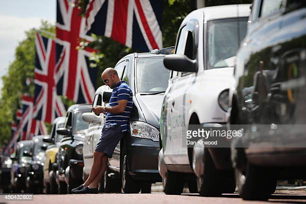 London taxi driver looks at his phone on The Mall during a protest against a new smart phone app 'Uber' on June 11 2014 in London England London's...