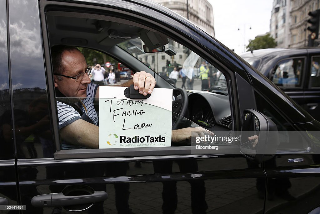 A London taxi driver places an identification board reading ' Totally Failing London' on the driver's window of his cab during a protest against Uber Technologies Inc.'s car sharing service in London, U.K., on Wednesday, June 11, 2014. Traffic snarled in parts of Madrid and Paris today, with a total of more than 30,000 taxi and limo drivers from London to Berlin blocking tourist centers and shopping districts. Photographer: Simon Dawson/Bloomberg via Getty Images