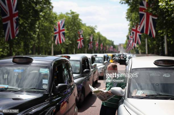 London taxi driver reads a newspaper on The Mall during a protest against a new smart phone app 'Uber' on June 11 2014 in London England London's...