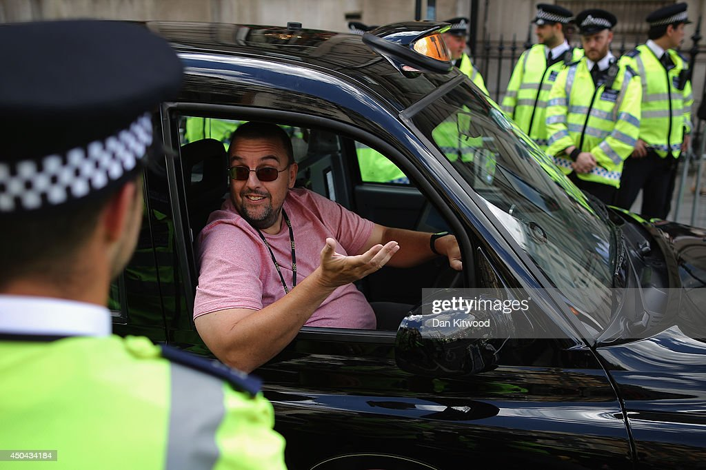 A London taxi driver speaks with Police Officers during a protest against a new smart phone app, 'Uber' on June 11, 2014 in London, England. London's licensed black taxi drivers are campaigning against the introduction of the 'Uber' taxi smartphone app in the United kingdom. Drivers say that there is a lack of regulation behind the new app.