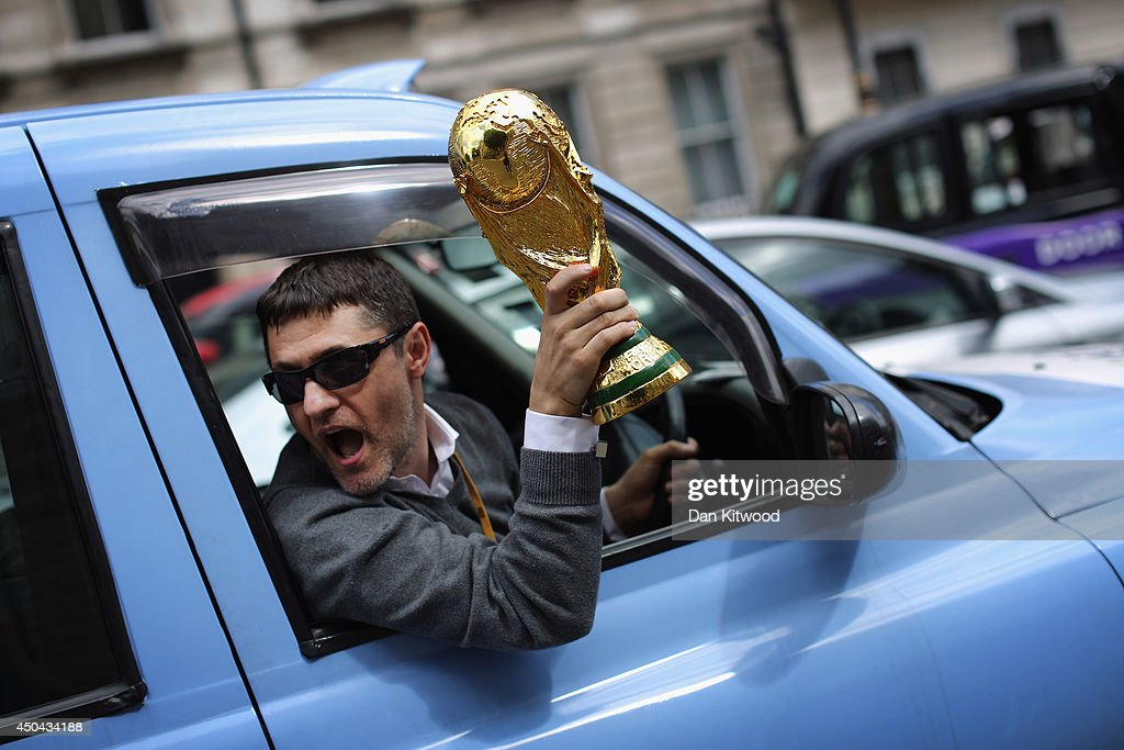 A London taxi driver waves a replica World Cup out of his cab during a protest against a new smart phone app, 'Uber' on June 11, 2014 in London, England. London's licensed black taxi drivers are campaigning against the introduction of the 'Uber' taxi smartphone app in the United kingdom. Drivers say that there is a lack of regulation behind the new app.
