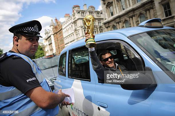 London taxi driver waves a replica World Cup out of his cab during a protest against a new smart phone app 'Uber' on June 11 2014 in London England...