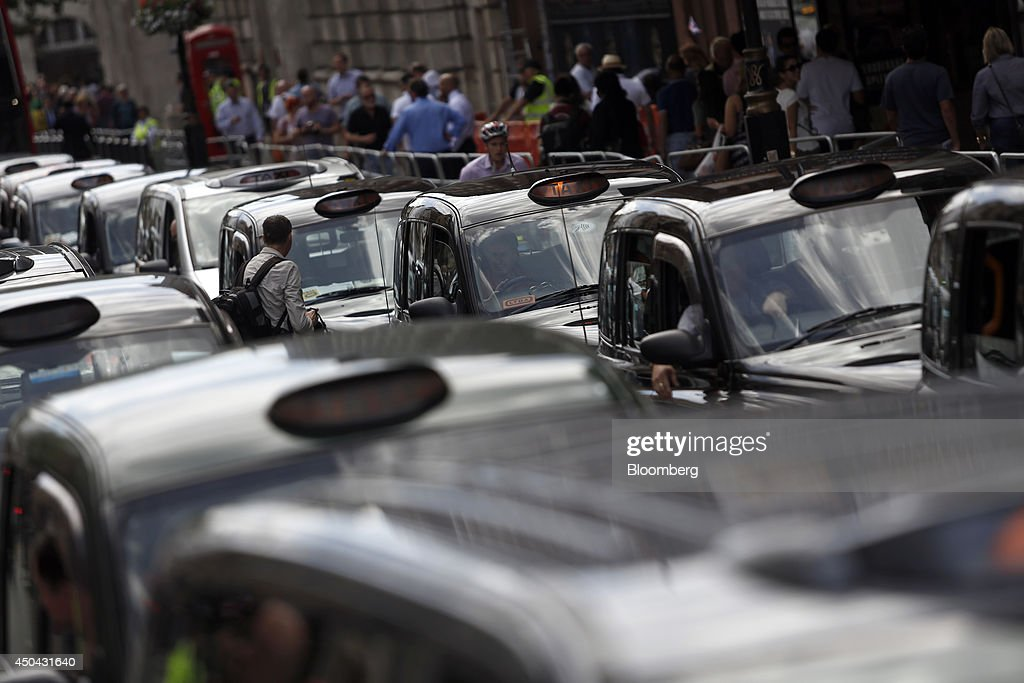 London taxi drivers sit in their parked cabs on Whitehall during a protest against Uber Technologies Inc.'s car sharing service in London, U.K., on Wednesday, June 11, 2014. Traffic snarled in parts of Madrid and Paris today, with a total of more than 30,000 taxi and limo drivers from London to Berlin blocking tourist centers and shopping districts. Photographer: Simon Dawson/Bloomberg via Getty Images