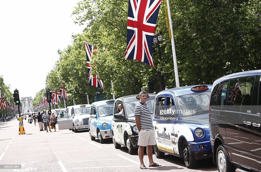 London taxi drivers stand alongside their parked cabs beneath British Union flags draped along The Mall, leading away from Buckingham Palace, during a protest against Uber Technologies Inc.'s car sharing service in London, U.K., on Wednesday, June 11, 2014. Traffic snarled in parts of Madrid and Paris today, with a total of more than 30,000 taxi and limo drivers from London to Berlin blocking tourist centers and shopping districts. Photographer: Simon Dawson/Bloomberg via Getty Images