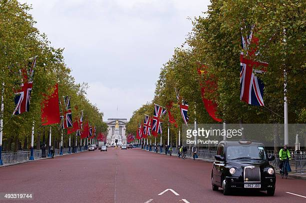 London taxi drives along The Mall which is lined with The British Union Jack flag and the Chinese Wu Xing Hong Qi flag ahead of the Chinese State...