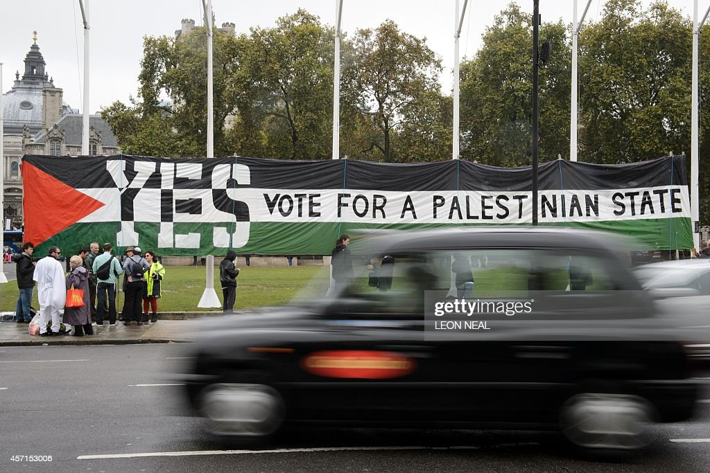 A London taxi drives by as ProPalestinian supporters position a giant banner calling for a recognised Palestinian State in Parliament Square central...