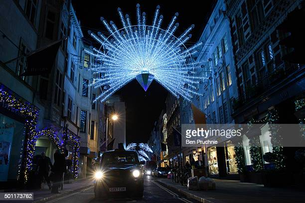 London taxi drives past the Christmas lighting displays on Bond Street on December 8 2015 in London England British retailers are hoping for a rise...