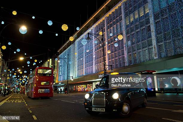 London taxi drives past the Christmas lighting displays on Oxford Street on December 8 2015 in London England British retailers are hoping for a rise...