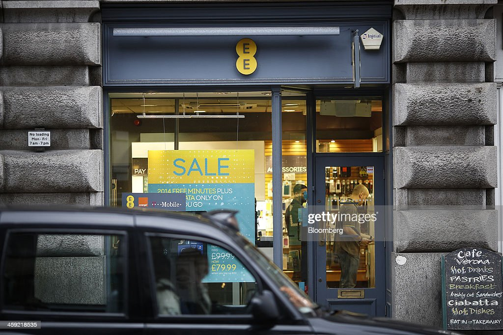 A London taxi passes an EE mobile phone store as customer browse inside in London, U.K., on Tuesday, Dec. 24, 2013. Vodafone Group Plc; EE, which is co-owned by Orange SA and Deutsche Telekom AG; Three, owned by Hutchison Whampoa Ltd.; and Virgin Media Inc. said they will cap bills run up on phones reported lost or stolen, stop mid-contract price increases, and support the U.K. government in its attempt to end roaming charges within the European Union. Photographer: Simon Dawson/Bloomberg via Getty Images