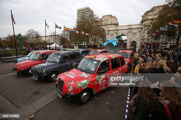 London taxis covered in iconic Cath Kidston prints burst out of a giant Christmas present at Marble Arch to celebrate the opening of the largest Cath...