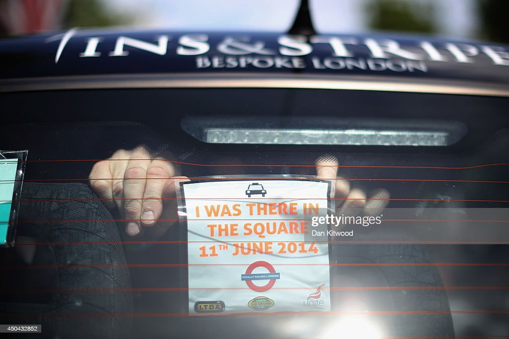 A London taxi's driver attaches a sticker to the back of his cab on The Mall during a protest against a new smart phone app, 'Uber' on June 11, 2014 in London, England. London's licensed black taxi drivers are campaigning against the introduction of the 'Uber' taxi smartphone app in the United kingdom. Drivers say that there is a lack of regulation behind the new app.