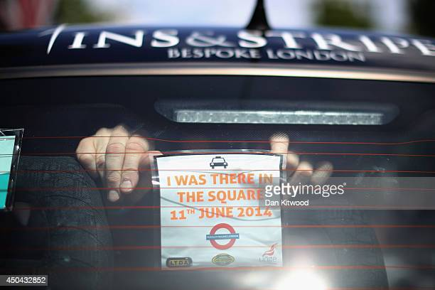 London taxi's driver attaches a sticker to the back of his cab on The Mall during a protest against a new smart phone app 'Uber' on June 11 2014 in...