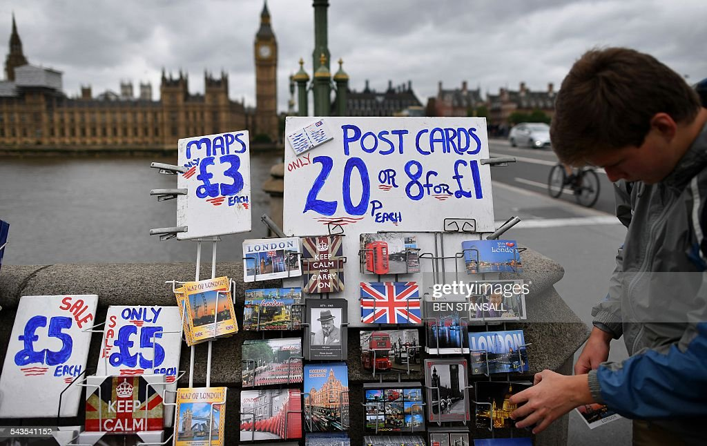 London themed postcards, including some depicting the Union flag, are displayed for sale near the Houses of Parliament in central London on June 29, 2016. Europe's leaders meet Wednesday without Britain for the first time following its shock decision to leave the EU, trying to pick up the pieces and prevent further disintegration. Britain has been pitched into uncertainty by the result of the June 23 referendum, with Cameron announcing his resignation, the economy facing a string of shocks and Scotland making a fresh threat to break away. / AFP / BEN