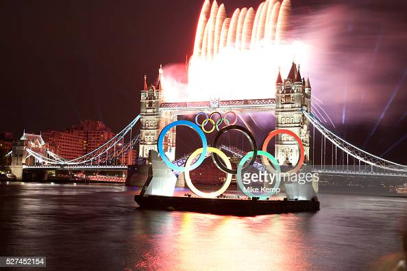 London UK Friday 27th July 2012 Olympic flame passes Tower Bridge with fireworks on way to the opening ceremony London's greatest landmark bridge...