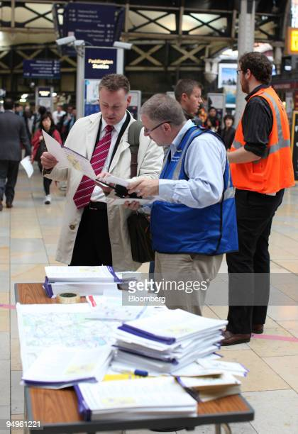 London Underground employee assists a passenger with travel information at Paddington Station on the second day of a Tube strike in London UK on...