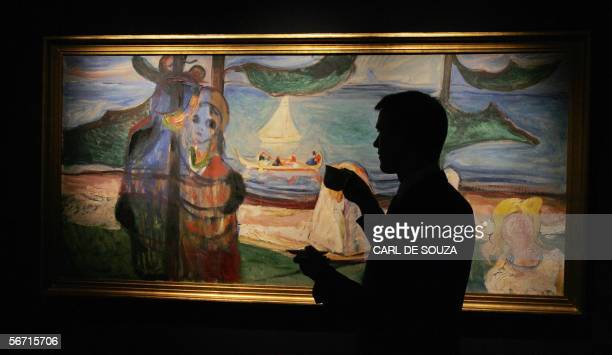 A man studies a painting entitled 'Summer Day' by Norwegian artist Edvard Munch at the Sotheby's auction house in London 01 February 2006 The...