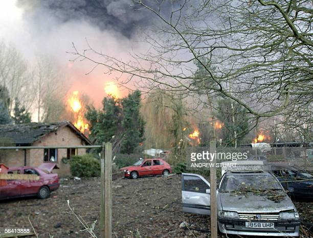 A view of the remains of farm buildings at Highgrange and Punchbowl Lane as smoke and flames billow from Buncefield oil distribution depot near Hemel...