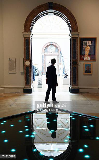 A visitor walks past an installation 'Time in Water' a work comprising waterproof LEDs submerged in water on show at the Summer Exhibition at The...