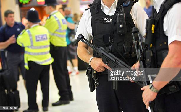 Armed police officers patrol Victoria Station in London 02 August 2005 on the day Britain's Prime Minister Tony Blair said a taskforce will be set up...