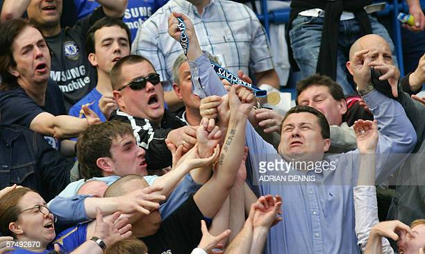 Chelsea supporters scramble to grab Manager Jose Mourinho's winners medal after he tossed it into the crowd during the celebrations after his team...