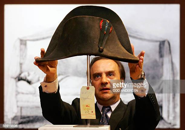 Christie's Director Nicholas Lambourn adjusts a hat once belonging to Napoleon Bonaparte in front of a sketch of Napoleon lying in state at...