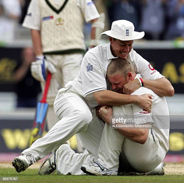 England's Ashley Giles congratulates bowler Andrew Flintoff after the dismissal of Australia's Shane Warne by Flintoff on the fourth day of the fifth...