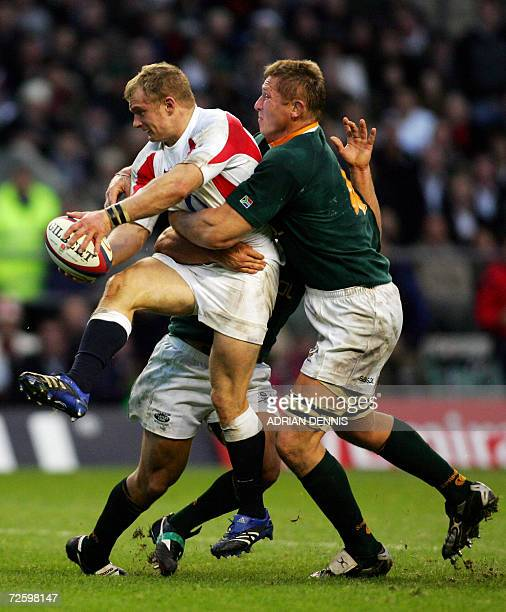England's Centre Jamie Noon gets held up in a tackle from South Africa's Lock Johan Ackermann during the Investec Challenge international test match...