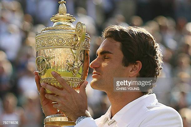 Roger Federer of Switzerland holds the trophy after defeating Rafael Nadal of Spain during the final of the Wimbledon Tennis Championships in...