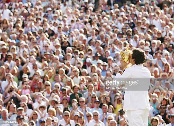 Roger Federer of Switzerland kisses the trophy after defeating Rafael Nadal of Spain during the final of the Wimbledon Tennis Championships in...
