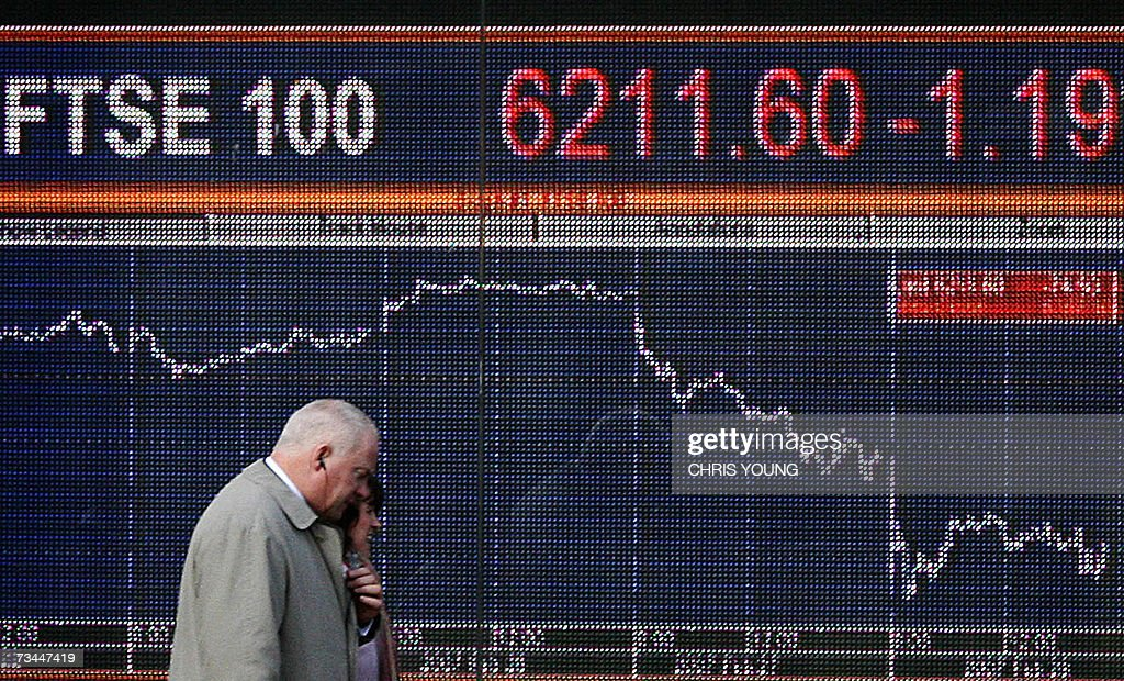 Unidentified business people walk past a financial information board in west London, 28 February 2007. Europe's main stock markets extended heavy losses in early deals on Wednesday, mirroring a slump across world indices caused by fears of an US economic slowdown and possible end to China's economic boom. At mid-day, London's FTSE 100 index of leading shares showed a drop of 0.91 percent to 6,229.10 points. AFP PHOTO/CHRIS YOUNG