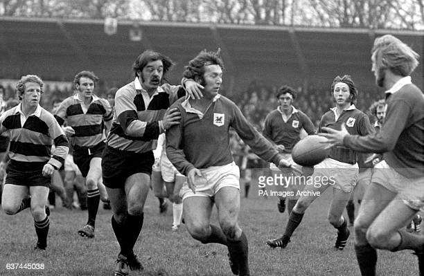 London Welsh's John Dawes lays the ball back to teammate Jim Shanklin under pressure from Newport's P Evans as teammate JPR Williams looks on