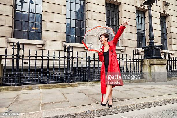 London Woman in Red Hailing a Taxi Cab