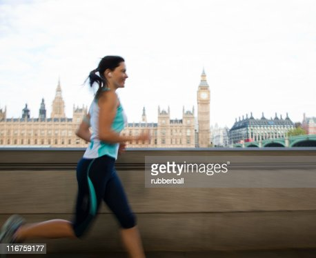 UK, London, Woman running in front of Westminster skyline : Stock Photo
