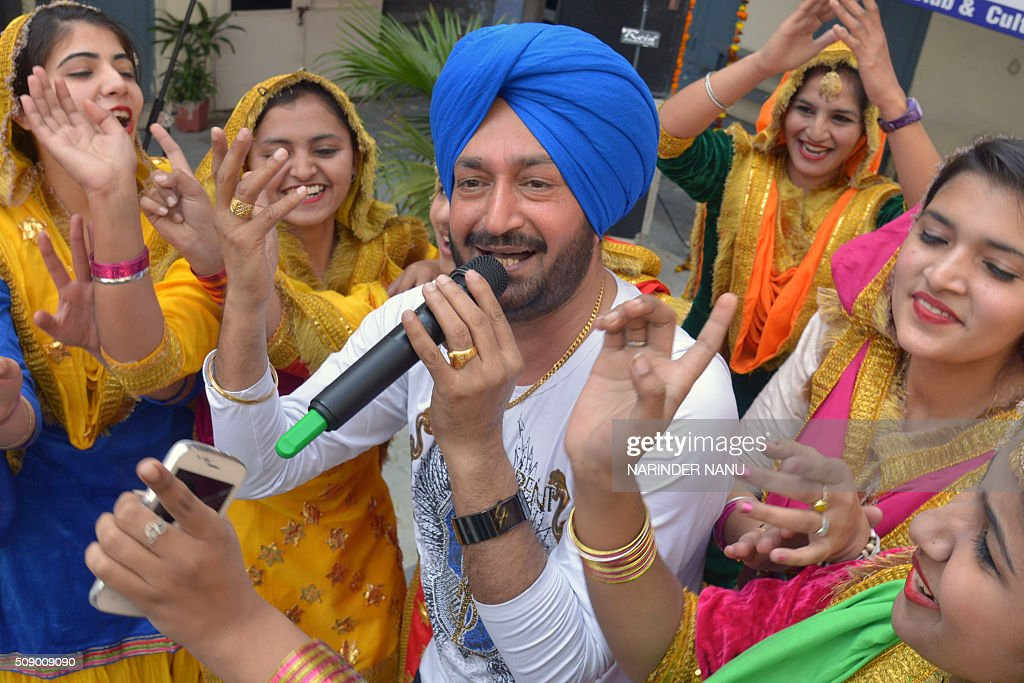 London-based Punjabi pop singer Malkit Singh (C) performs during a promotional event at a college in Amritsar on February 8, 2016. Malkit Singh visited the city for the promotion of his new music album Yaari Jatta Di. AFP PHOTO / NARINDER NANU / AFP / NARINDER NANU