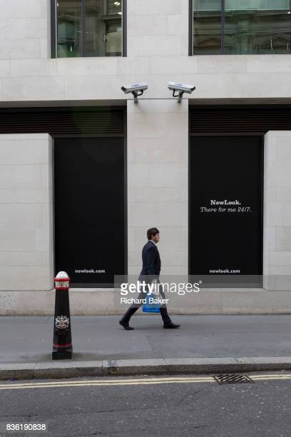 A Londoner walks beneath two CCTV cameras in the City of London one of the mostwatched cities in the world on 11th August in London England According...