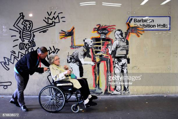 Londoners admire street art created in September 2017 near the Barbican Centre in London England by Banksy an anonymous Englandbased graffiti artist...