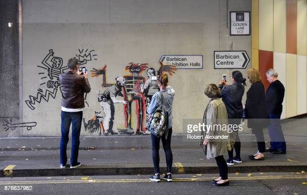 Londoners and visitors admire and photograph street art created in September 2017 near the Barbican Centre in London England by Banksy an anonymous...