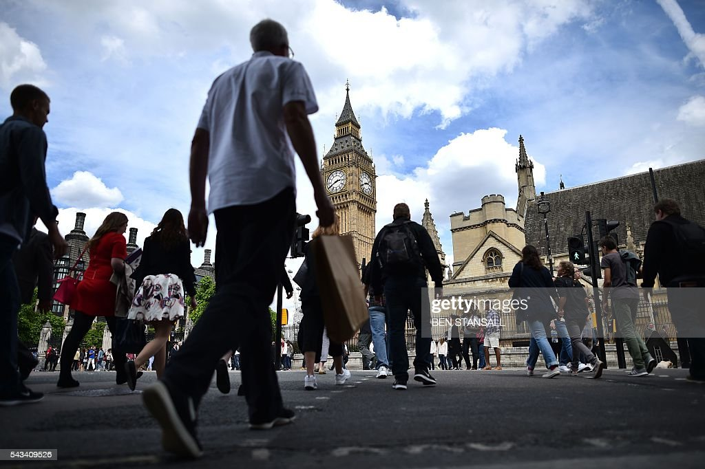 Londoners cross the road near the Elizabeth Tower (C) which houses the 'Big Ben' bell in the Palace of Westminster in central London on June 28, 2016. EU leaders attempted to rescue the European project and Prime Minister David Cameron sought to calm fears over Britain's vote to leave the bloc as ratings agencies downgraded the country. Britain has been pitched into uncertainty by the June 23 referendum result, with Cameron announcing his resignation, the economy facing a string of shocks and Scotland making a fresh threat to break away. / AFP / BEN