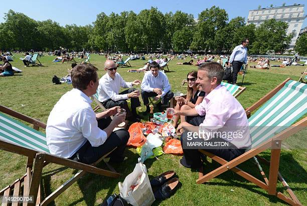 Londoners enjoy the sun as they hold a picnic lunch at Green Park in central London on July 26 2012 Sunny weather has returned to Britain in time for...