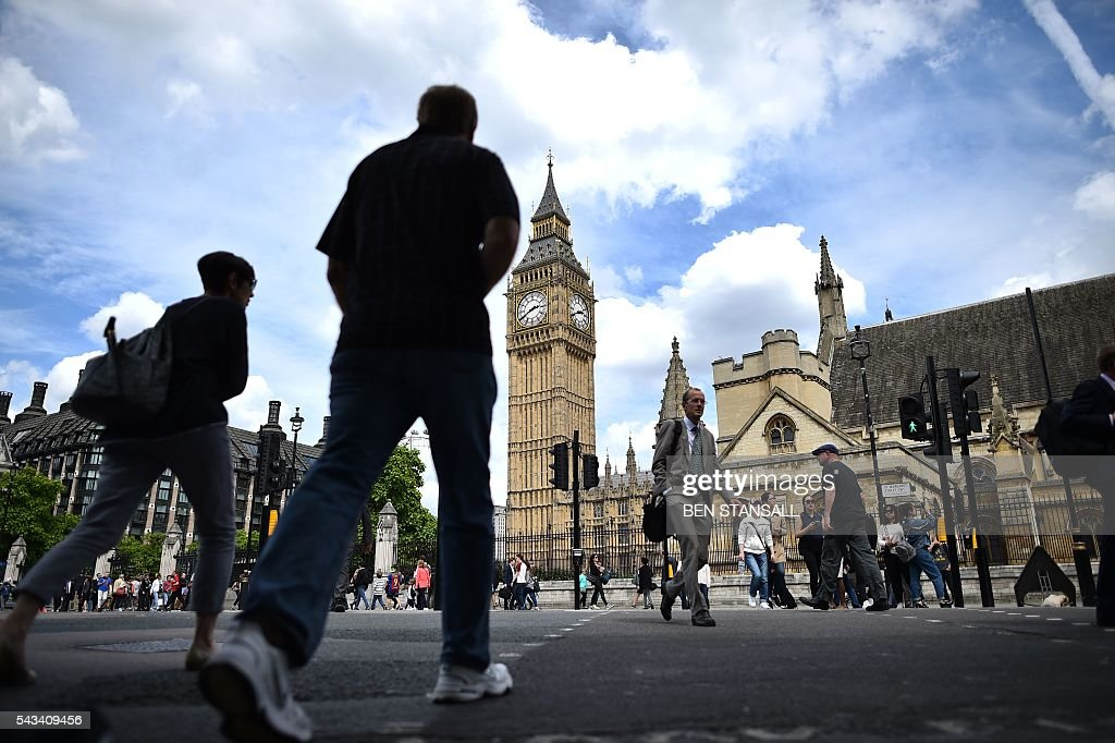 Londoners pass the Elizabeth Tower (C) which houses the 'Big Ben' bell in the Palace of Westminster in central London on June 28, 2016. EU leaders attempted to rescue the European project and Prime Minister David Cameron sought to calm fears over Britain's vote to leave the bloc as ratings agencies downgraded the country. Britain has been pitched into uncertainty by the June 23 referendum result, with Cameron announcing his resignation, the economy facing a string of shocks and Scotland making a fresh threat to break away. / AFP / BEN
