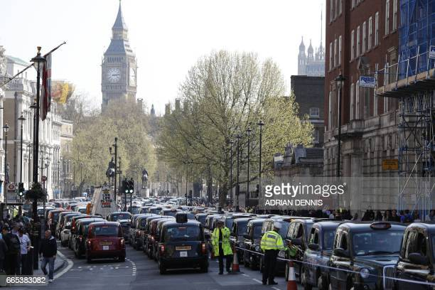 London's black cab drivers block Whitehall during a demonstration over the regulation private hire cars using the Uber app in London on April 6 2017...