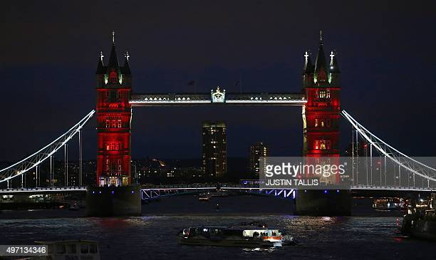 London's iconic Tower Bridge is illuminated in blue white and red lights resembling the colours of the French national flag in London on November 14...
