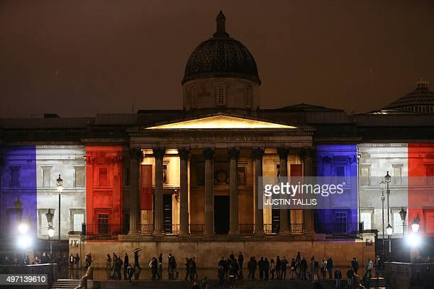 London's National Gallery is illuminated in blue white and red lights resembling the colours of the French national flag in London on November 14 as...