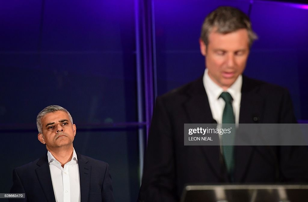 London's new Mayor Sadiq Khan (L) looks on as Conservative Party member Zac Goldsmith addresses the media following the announcement of Khan's election victory at City Hall in central London on May 7, 2016. London became the first EU capital with a Muslim mayor Friday as Sadiq Khan won the election that saw his opposition Labour party suffer nationwide setbacks. / AFP / LEON